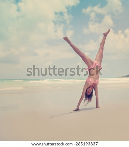 Beautiful young woman standing on hands on the beach, image with retro toning - stock photo