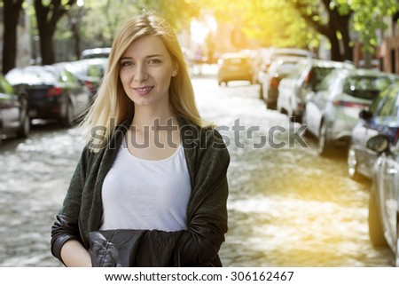 Beautiful young woman standing on the street smiling and looking at camera.  - stock photo