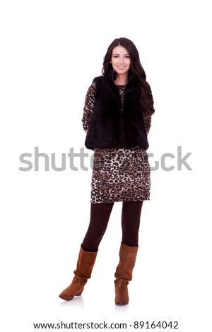 beautiful young woman standing on white background with her hands behind back - stock photo