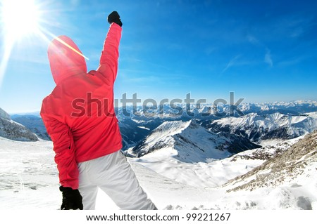 Beautiful young woman stands on top of the mountain with alps background - stock photo