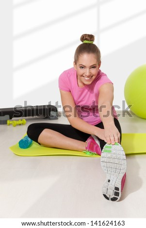 Beautiful young woman streching after workout, light background - stock photo