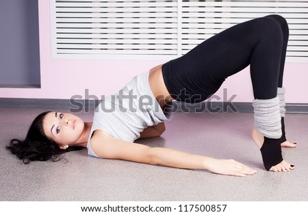 beautiful young  woman stretching the muscles of  legs  in the gym - stock photo