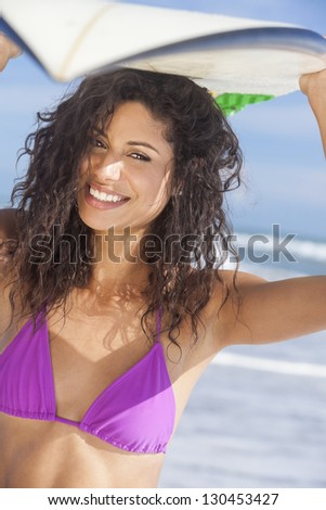 Beautiful young woman surfer girl in bikini with surfboard standing in the surf on a beach - stock photo