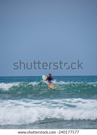 Beautiful young woman surfing in Kuta Bali - stock photo
