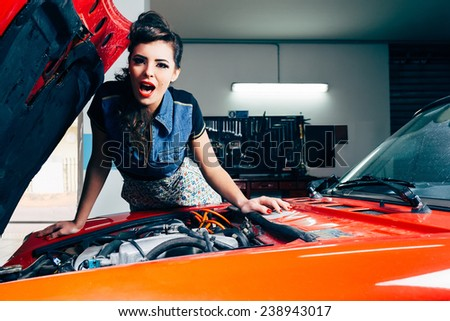 beautiful young woman surprised in car garage  - stock photo