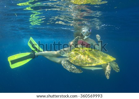 Beautiful young woman swims with Sea Turtle - stock photo