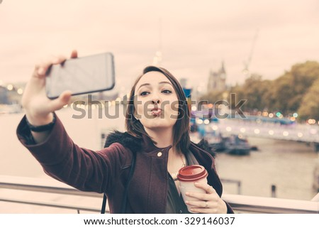 Beautiful young woman taking a selfie in London. She is holding the camera with one hand and looking at it smiling. She is also holding a cup of tea on the other hand. - stock photo