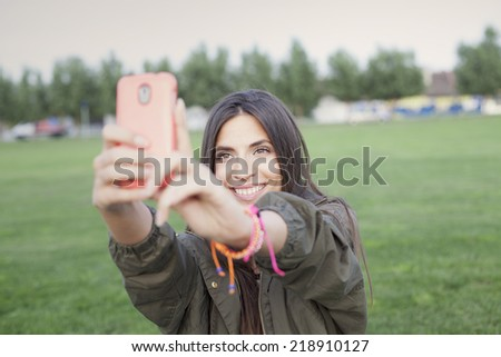 Beautiful young woman taking a selfie with phone - stock photo