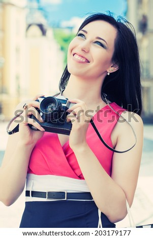 beautiful young woman taking photos with vintage camera on a city street - stock photo