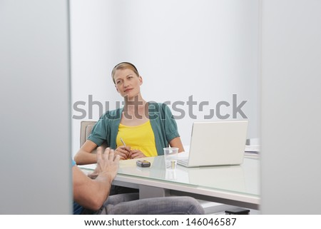 Beautiful young woman talking to cropped male colleague in office - stock photo