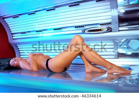 Beautiful young woman tanning in solarium - stock photo