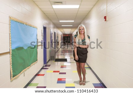 Beautiful young woman teacher at a grade elementary school hallway - stock photo