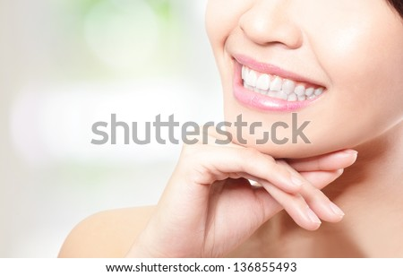 Beautiful young woman teeth close up with copy space on the left side. Isolated over green background, asian beauty model - stock photo