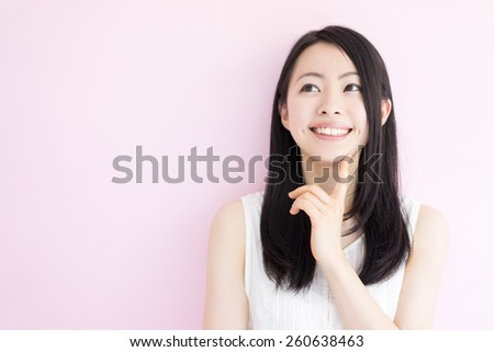 beautiful young woman thinking against pink background - stock photo