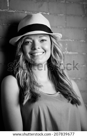 Beautiful Young Woman - This is a black and white image of a beautiful young woman wearing her fedora against a brick wall. - stock photo