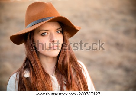 Beautiful Young Woman - This is a portrait of a beautiful young woman wearing a brimmed hat with a serious look on her face. - stock photo