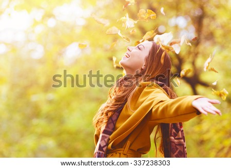 Beautiful young woman throwing leaves in a park, enjoying  - stock photo
