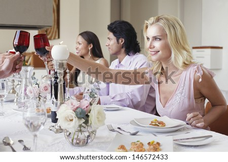 Beautiful young woman toasting red wine with friends at dinner table - stock photo
