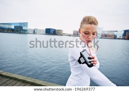 Beautiful young woman training outdoors while using a smartphone to monitor her progress. Caucasian female runner. - stock photo