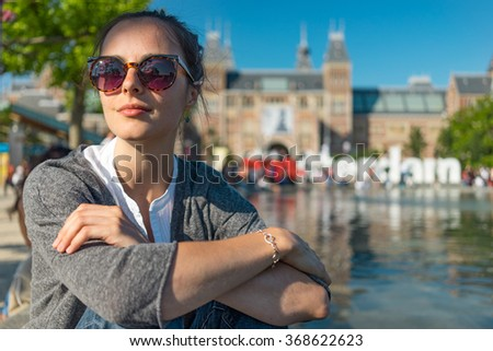 beautiful young woman traveler sitting on the water's edge admire Amsterdam Vondelpark beauties - stock photo