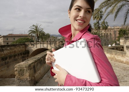 Beautiful young woman turning around while holding a laptop computer un her arms. - stock photo