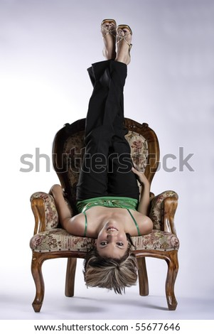 Beautiful young woman upside down on a chair - stock photo