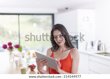 beautiful young woman using  a digital tablet in the kitchen - stock photo