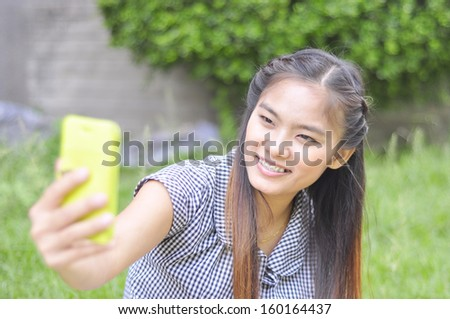 Beautiful young woman using a mobile phone. Portrait of asian - stock photo