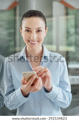 Beautiful young woman using a smart phone and leaning on a window, she is smiling at camera - stock photo
