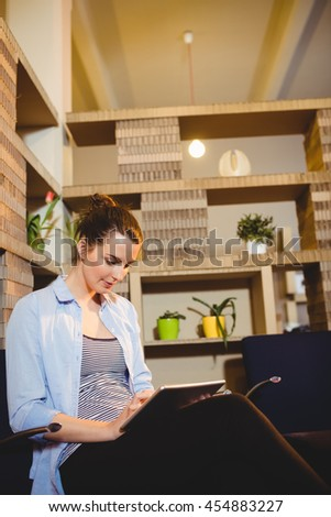 Beautiful young woman using digital tablet at office - stock photo