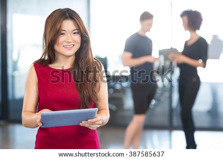 Beautiful young woman using digital tablet in the office - stock photo