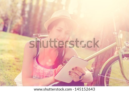 Beautiful young woman using digital tablet sitting next to her bike. - stock photo