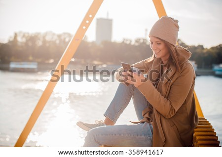 Beautiful young woman using her phone  - stock photo
