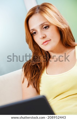 Beautiful Young Woman Using Laptop In Living Room - stock photo