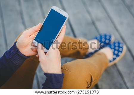 Beautiful young woman using smart phone at beach - stock photo