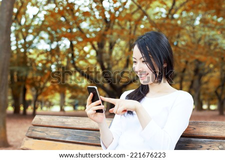 Beautiful young woman using smart phone on a bench in autumn park  - stock photo