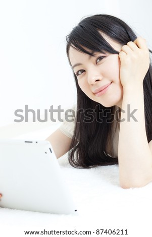 Beautiful young woman using tablet computer - stock photo