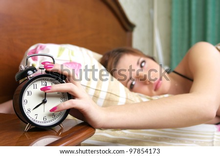 Beautiful young woman waking up, lying in bed and turning off alarm clock - stock photo