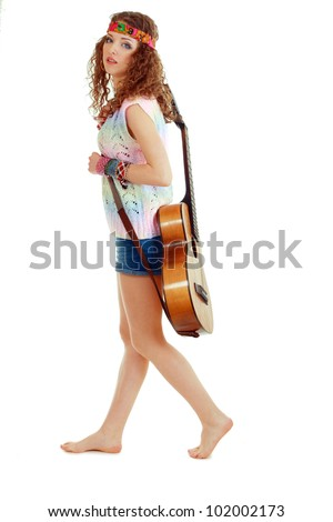 beautiful young woman waliking in hippie outfit with an acoustic guitar. Isolated on white - stock photo