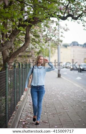 Beautiful young woman walking along a street - stock photo