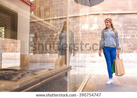 Beautiful young woman walking in city shopping street looking at store glass window with reflections, carrying shopping paper bags and smiling, outdoors. Teenager consumer lifestyle, sunny exterior. - stock photo