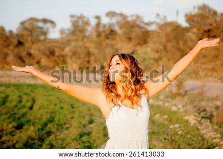 Beautiful young woman walking in the countryside with beautiful light - stock photo