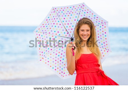 Beautiful Young Woman Walking on Tropical Beach with Colorful Umbrella - stock photo