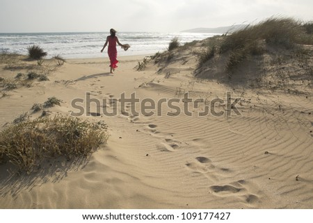 Beautiful young woman walking through the sand dunes towards  beach - stock photo