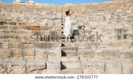 Beautiful young woman walking up the stone stairs - stock photo