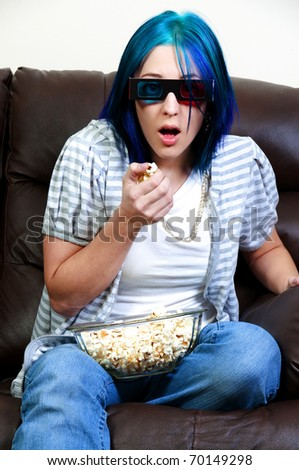 Beautiful young woman watching a 3d dvd movie on tv at home with popcorn - stock photo