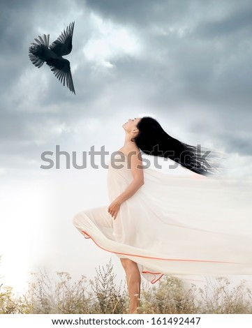 Beautiful young woman waving her hair opposite to flying bird. Freedom concept - stock photo