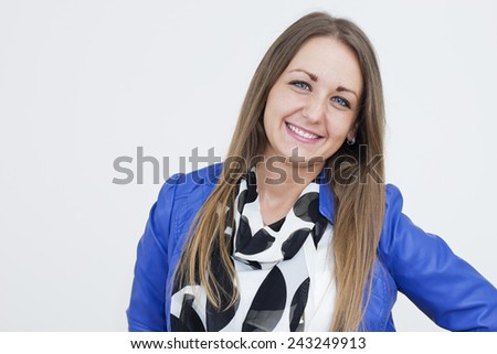 Beautiful young woman wearing a blue jacket smiling and looking at camera. - stock photo
