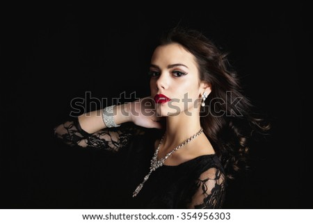 Beautiful young woman wearing a classic black lace dress and crystal jewelery with wind blown hair.  Shot on black background. - stock photo