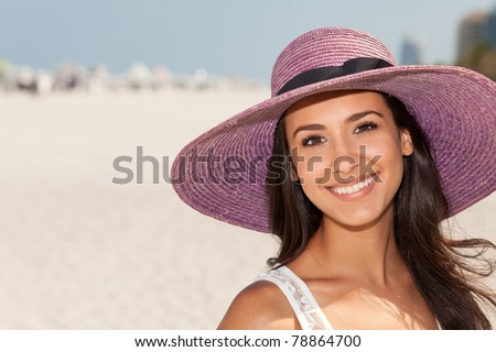 Beautiful young woman wearing a fancy purple hat and enjoying Miami's beautiful South Beach. - stock photo